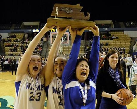 Braintree coach Kristen McDonnell (right) smiles as her captains show their championship trophy after the Division 1 girls' state basketball final.